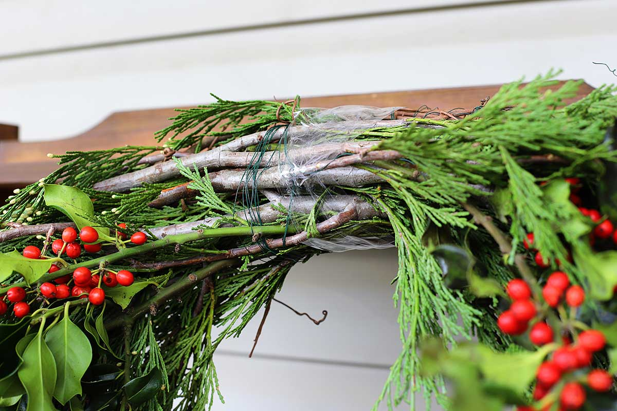 using packing tape to keep evergreens in place on wreath