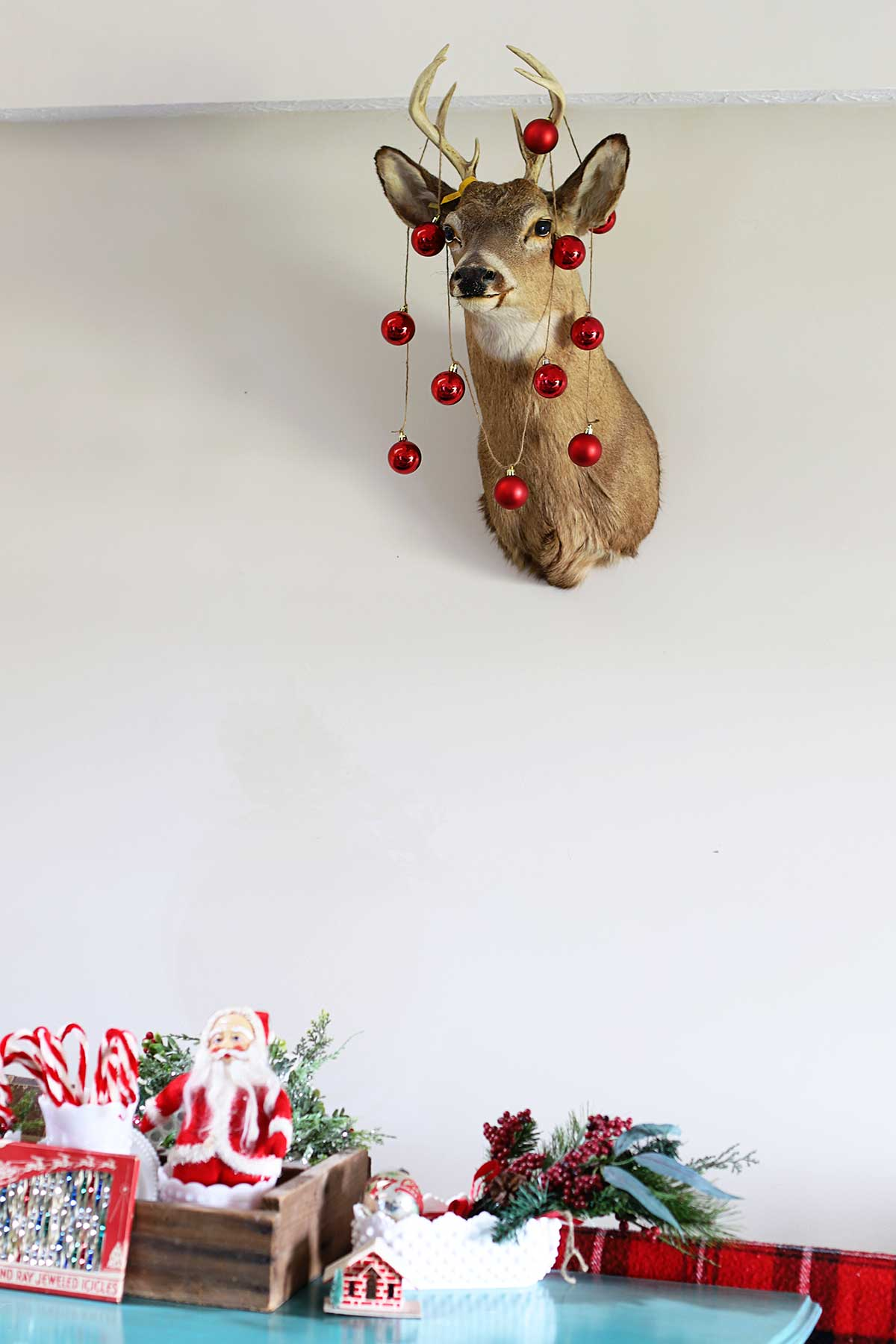 mounted deer head decorated for Christmas with round Christmas ornaments