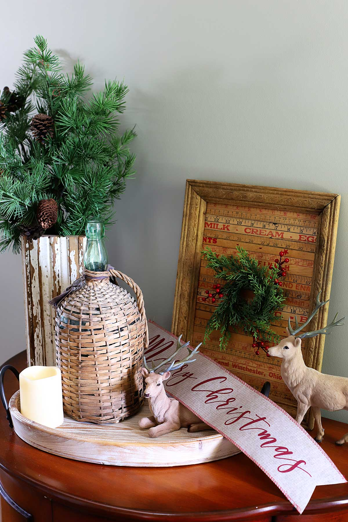 French country Christmas vignette with deer and demijohn