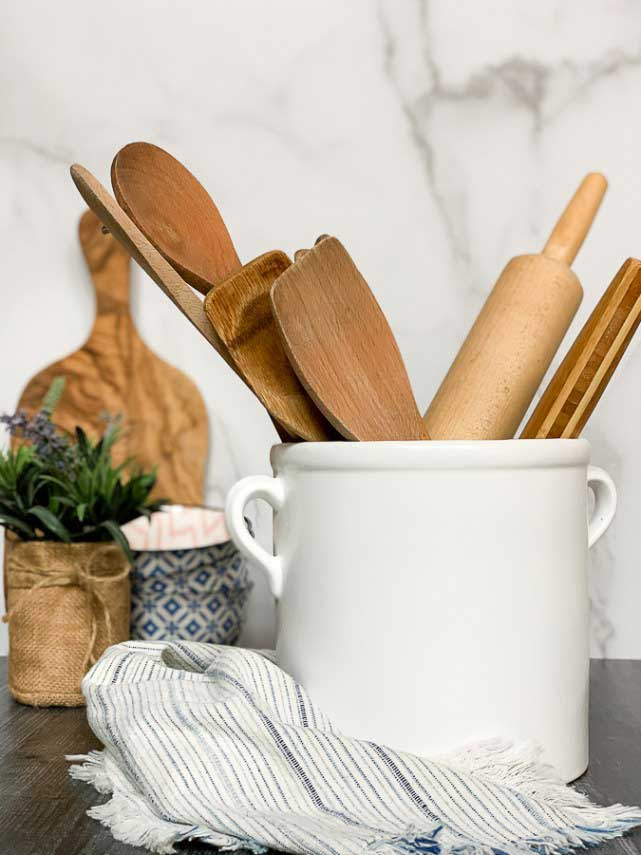 Farmhouse stoneware crock holding rolling pin and wooden kitchen utensils