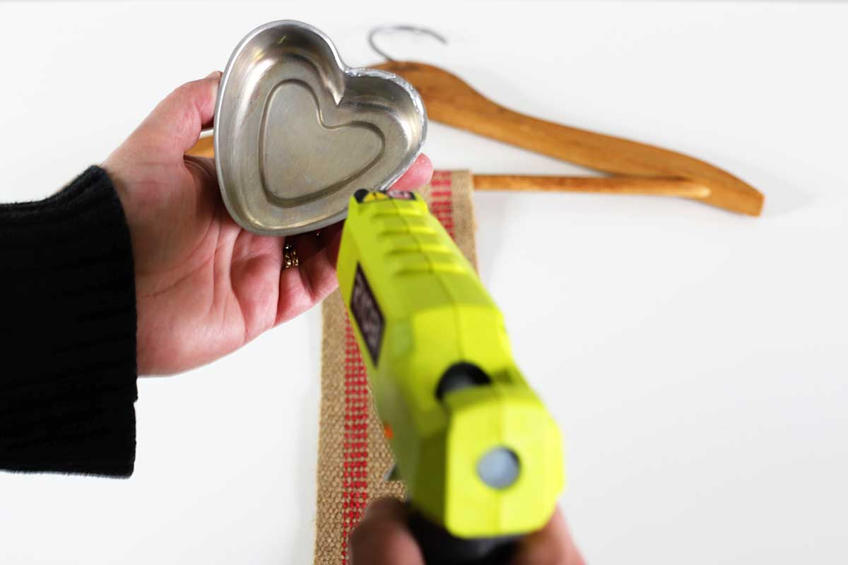 applying glue to underside of tin hearts used in Valentines Day banner