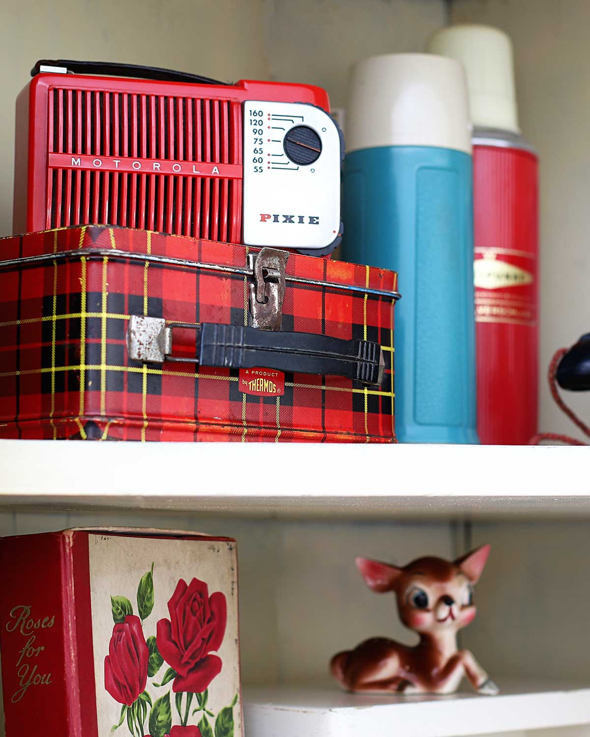 A red Motorola Pixie radio, vintage plaid school Thermos lunchbox and thermoses