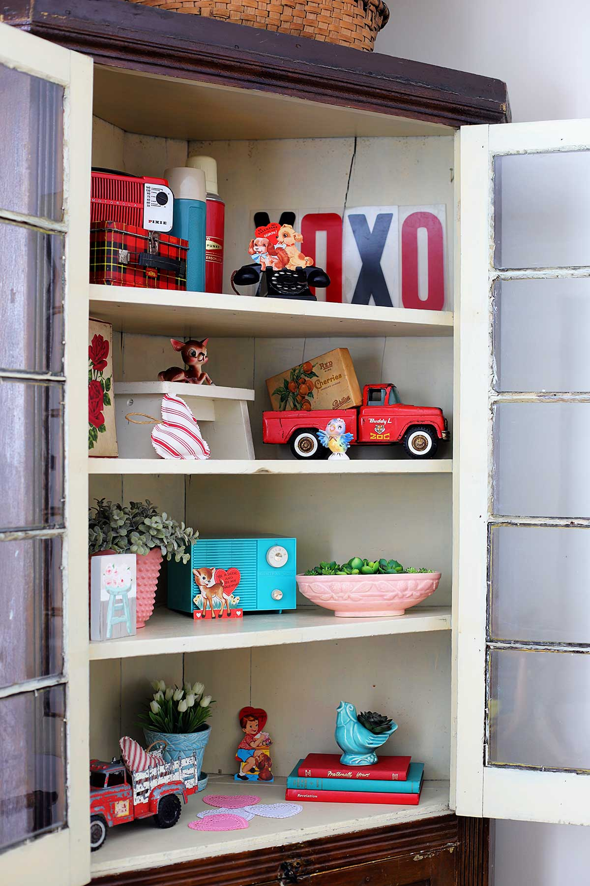 cabinet filled with vintage pottery, red trucks, classroom Valentines and more thrift store finds