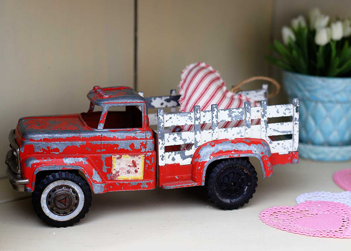 vintage red toy pickup truck with Valentines Day heart in the back