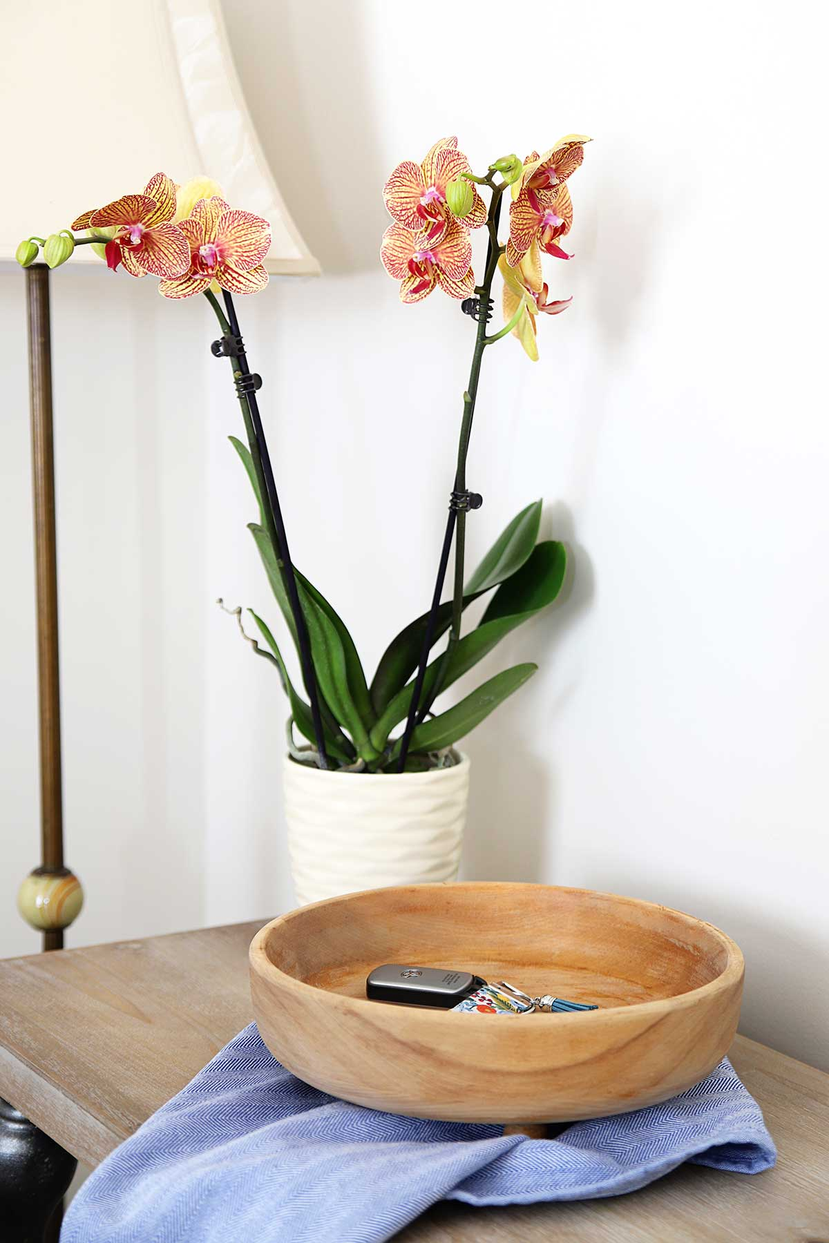 Bleached wooden bowl for farmhouse style sitting on counter with orchids