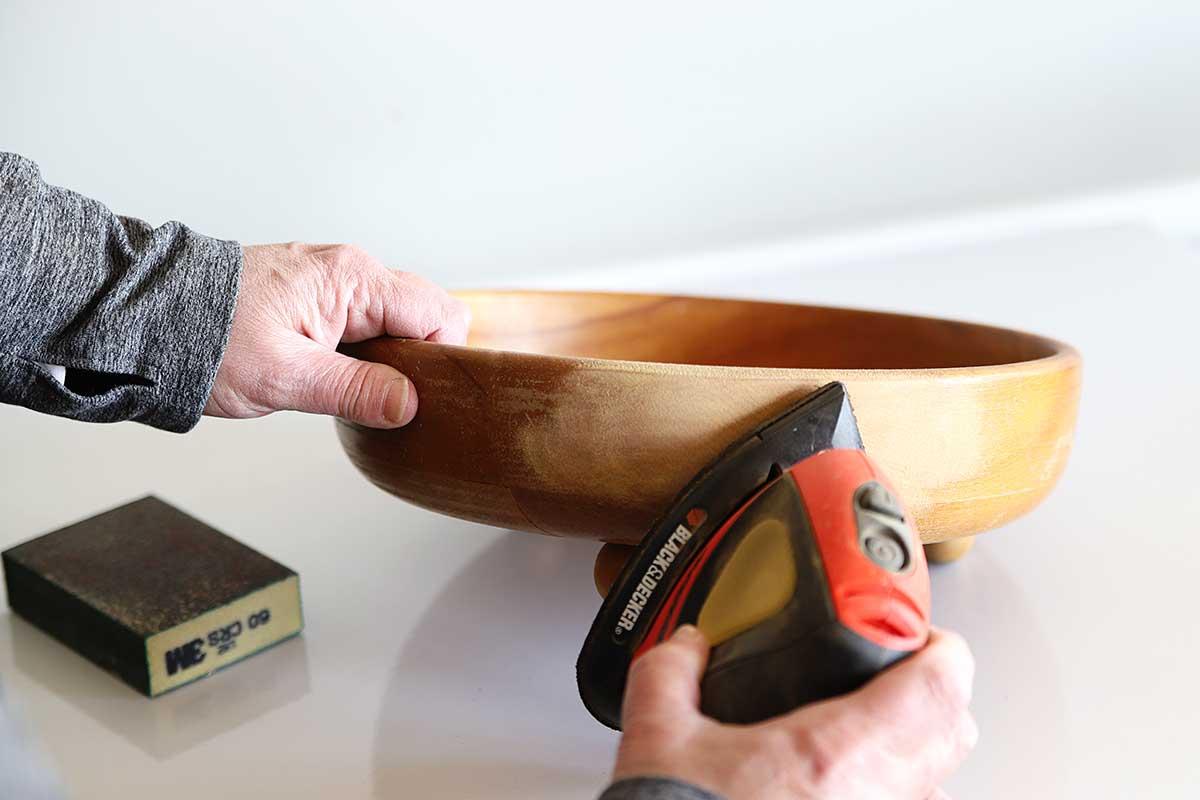 Sanding wooden bowl to prepare for bleaching