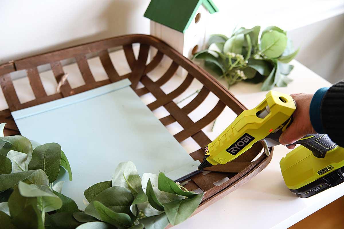 using hot glue gun to adhere eucalyptus leaves to spring basket wreath