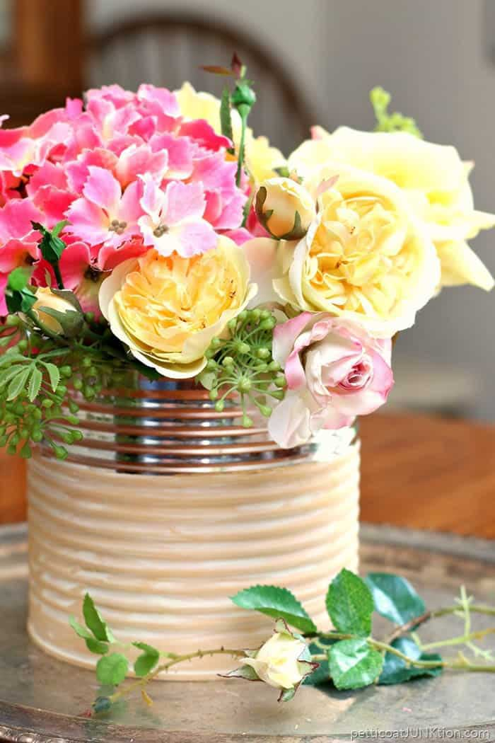 repurposed coffee can into a planter for budget friendly DIY garden project