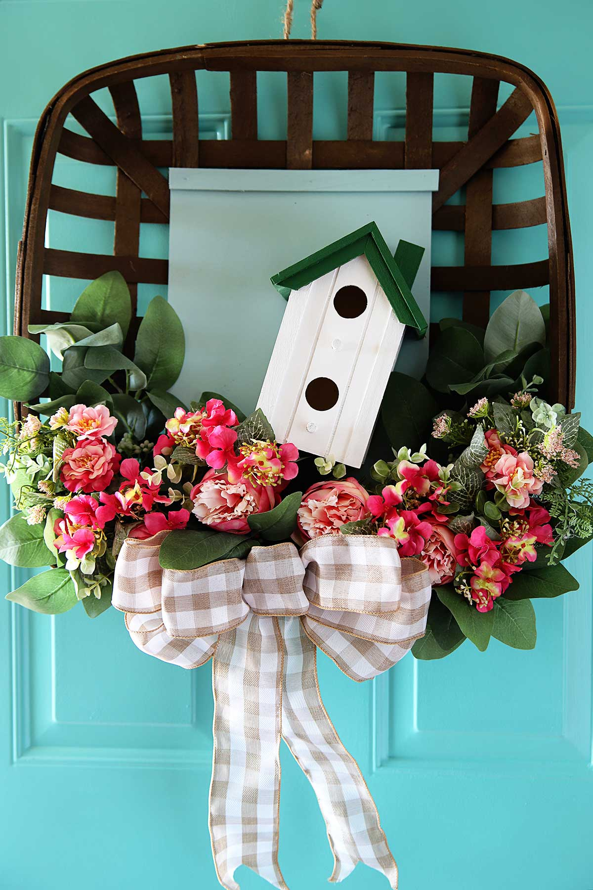upcycled spring wreath hanging on aqua front door