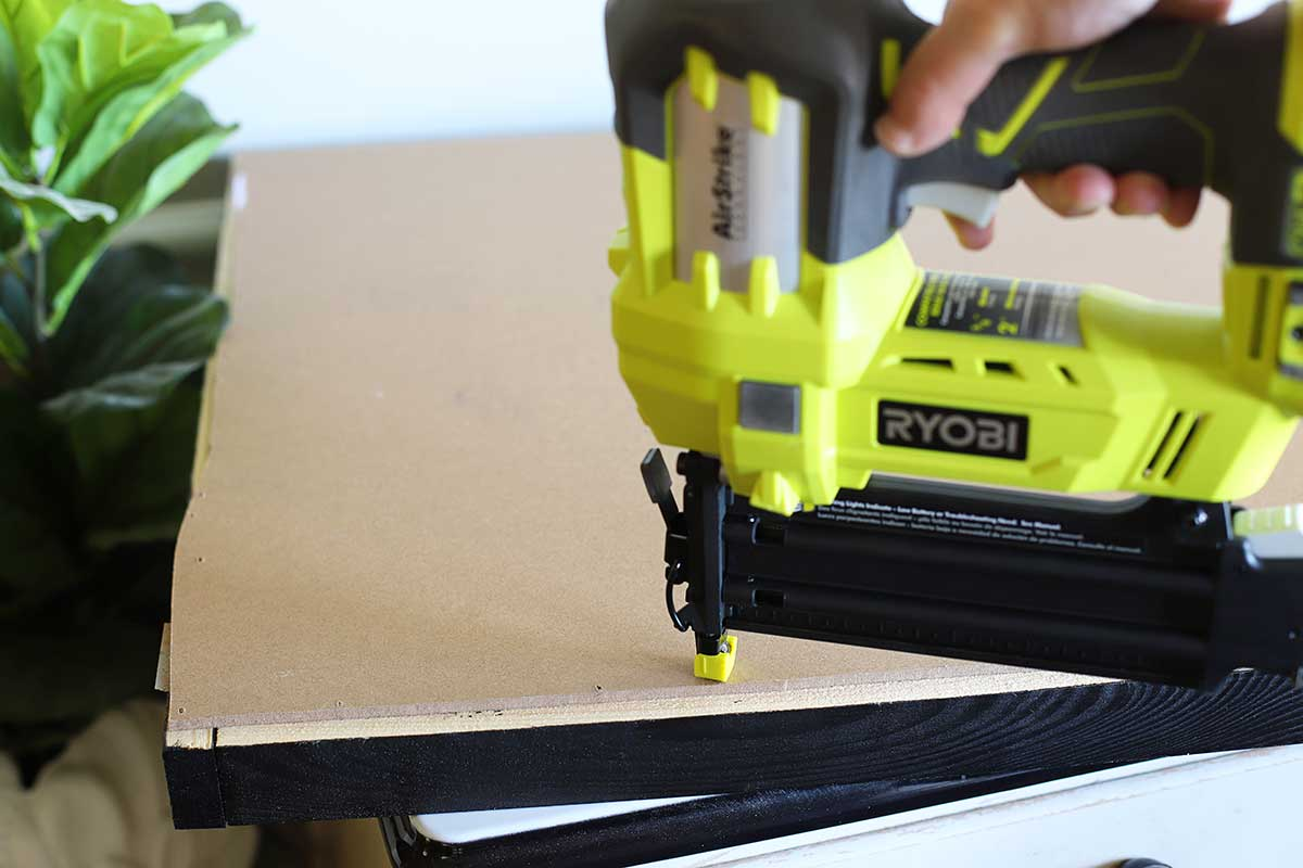 attaching poster to wood frame with brad nailer