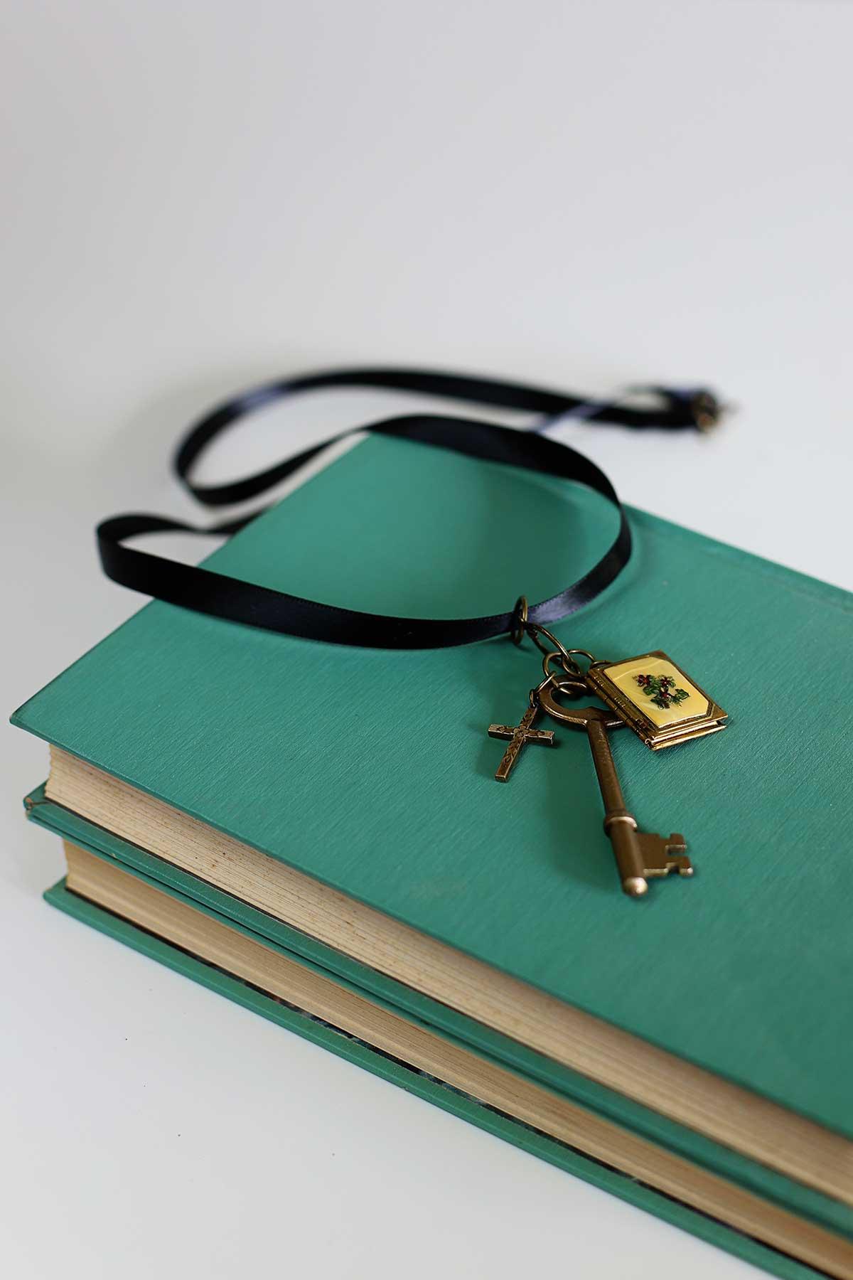 Colar com chave de esqueleto do vintage DIY sentado sobre uma pilha de livros aquáticos.