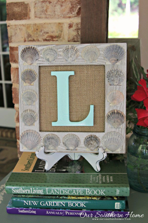 Wooden frame covered in sea shells with a monogram letter L.