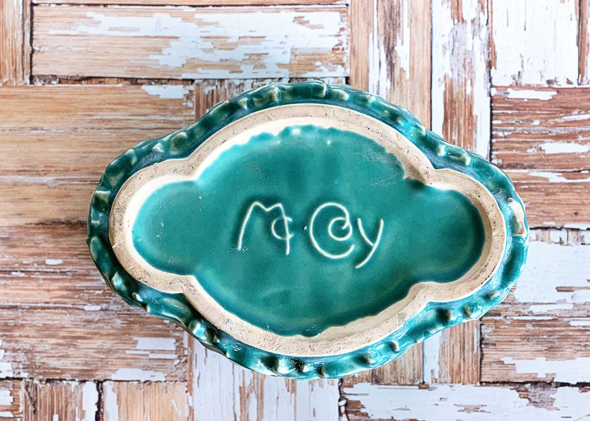 The McCoy Pottery mark on the bottom of a turquoise planter.