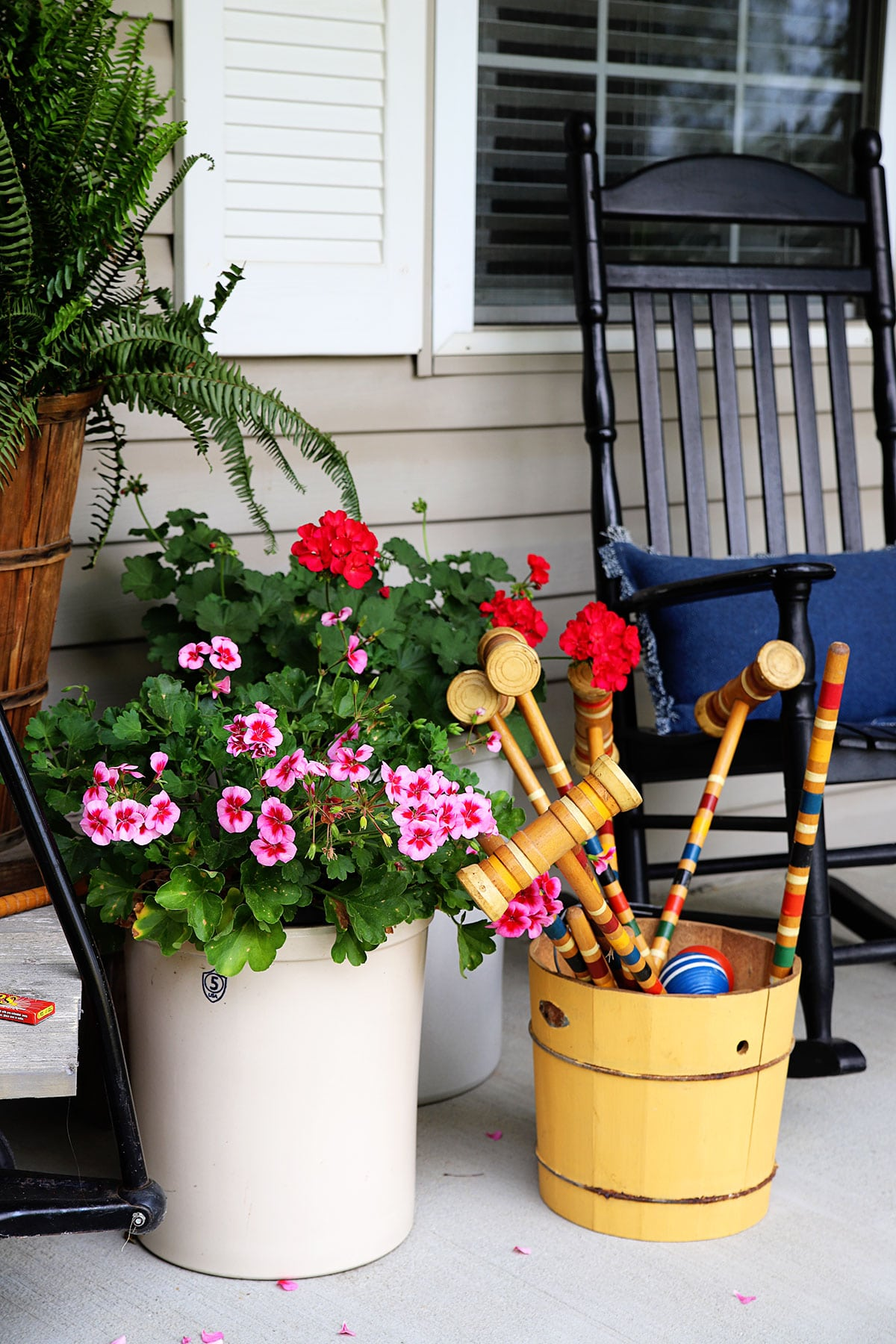 Geraniums planted in crocks on the front porch. Croquet set in a yellow ice cream churn to the side.