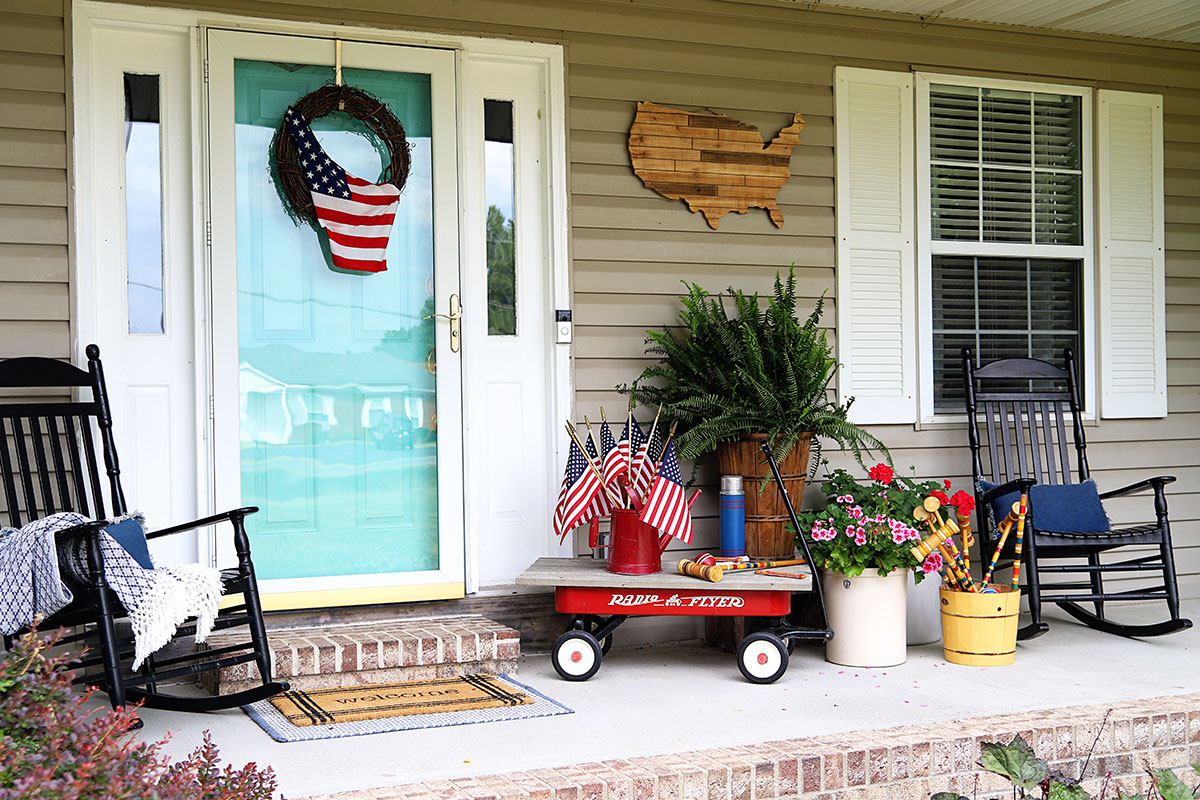 Porch decorated for the summer holidays - 4th Of July, Memorial Day and Labor Day. Decorated using vintage items, plants and flags.