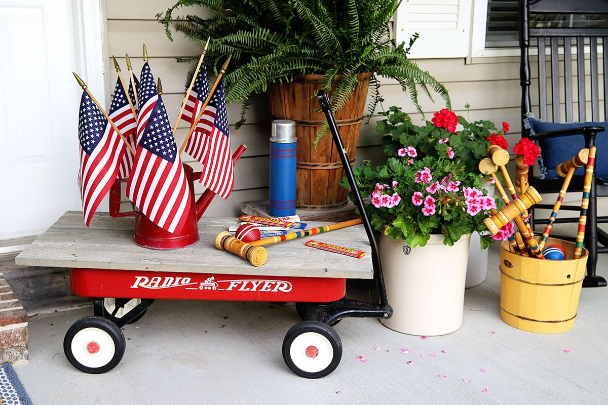 Radio Flyer wagon with a red watering can with flags in it.