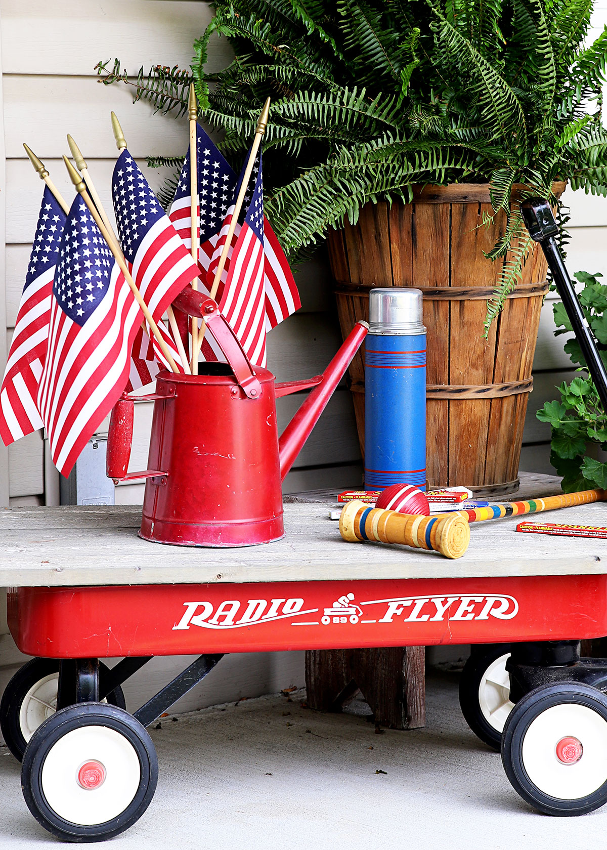 Red Radio Flyer wagon sitting on porch for Fourth Of July decorations.