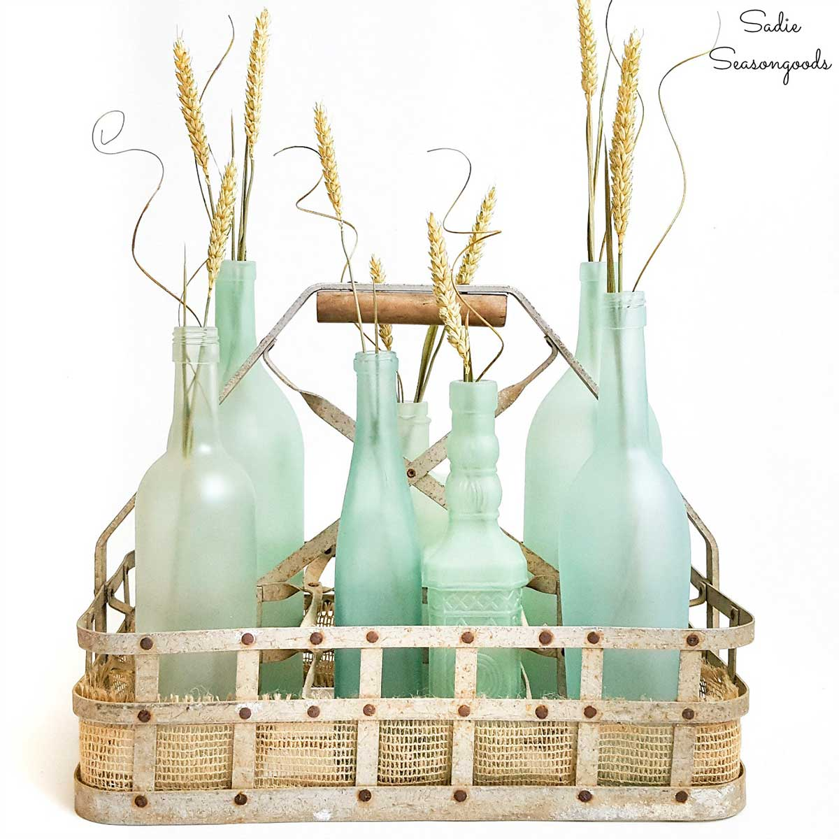 6 repurposed bottles painted in the color sea glass and sitting in a bottle carrier.