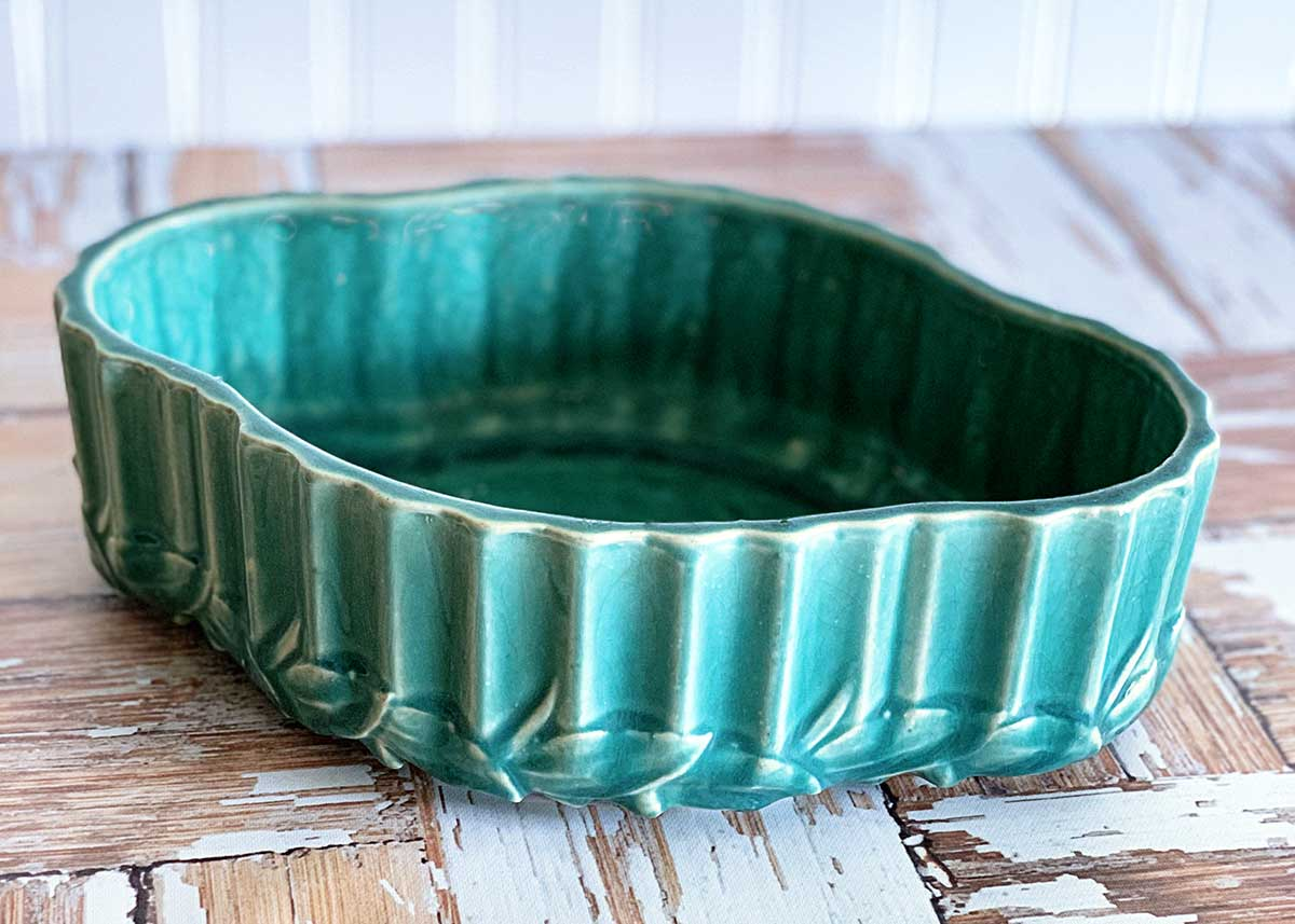 Turquoise colored McCoy pottery bulb bowl - shallow in design with ribs and leaves on the sides.