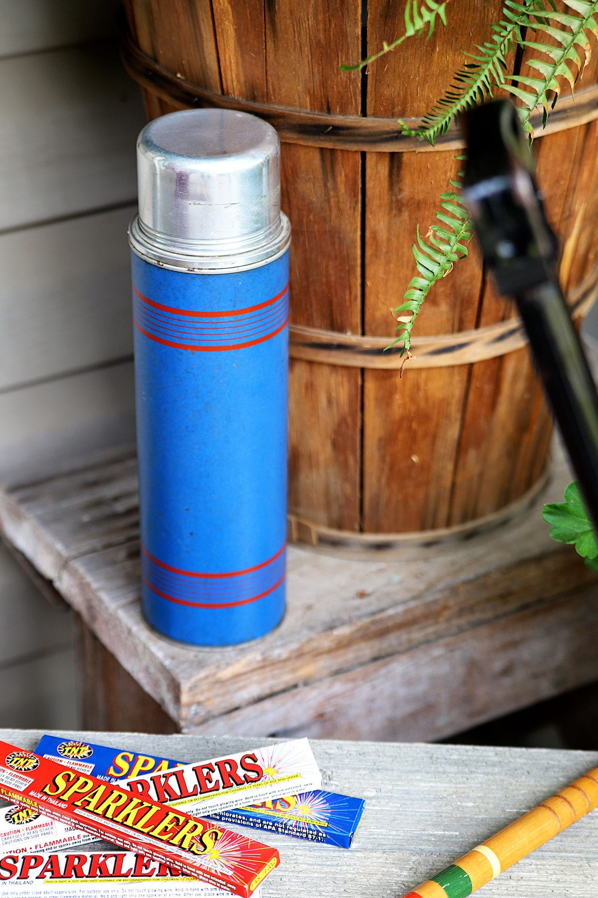 Blue vintage thermos sitting on bench as part of 4th Of July decorations.