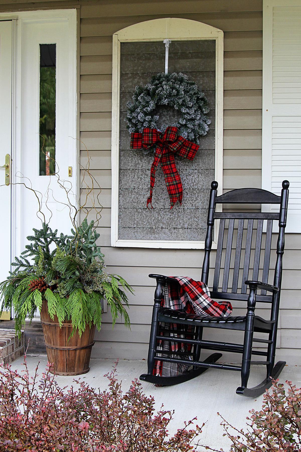 Cozy porch decor showing a black porch rocker with a plaid throw over the arm for winter porch decor.