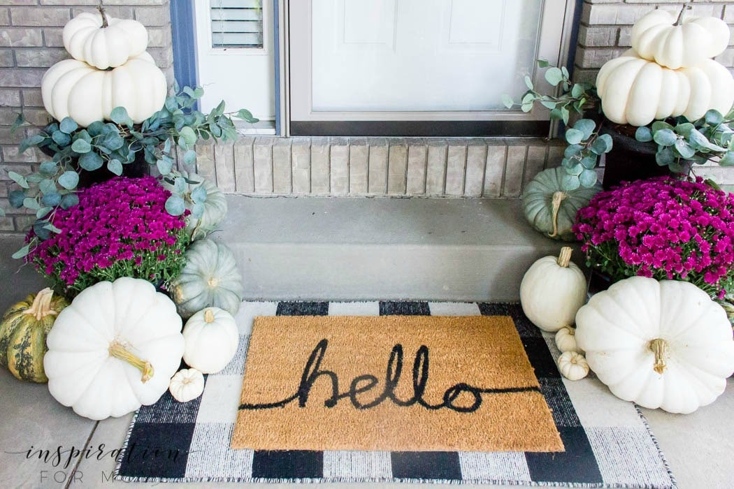 Layering a doormat that says hello onto a larger black and white buffalo check doormat.