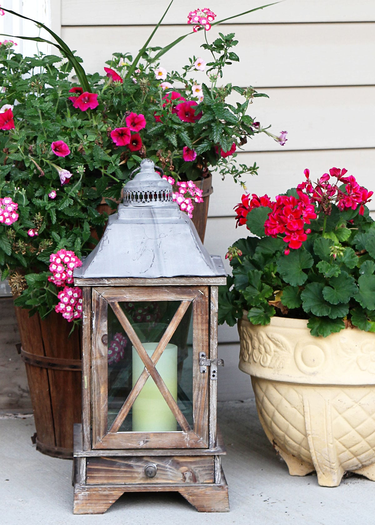 Wooden lantern featured on a small porch with a pink potted flowers.