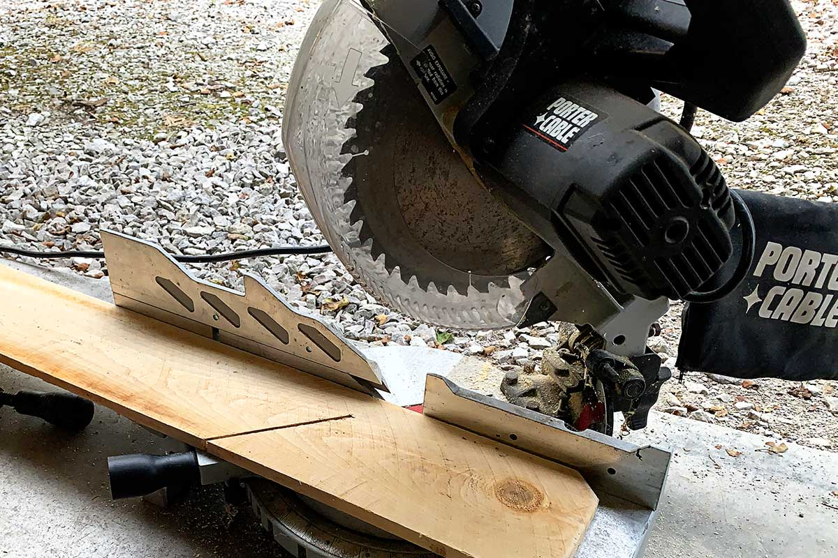 Using a miter saw to cut cedar fencing pickets to make angel wings.