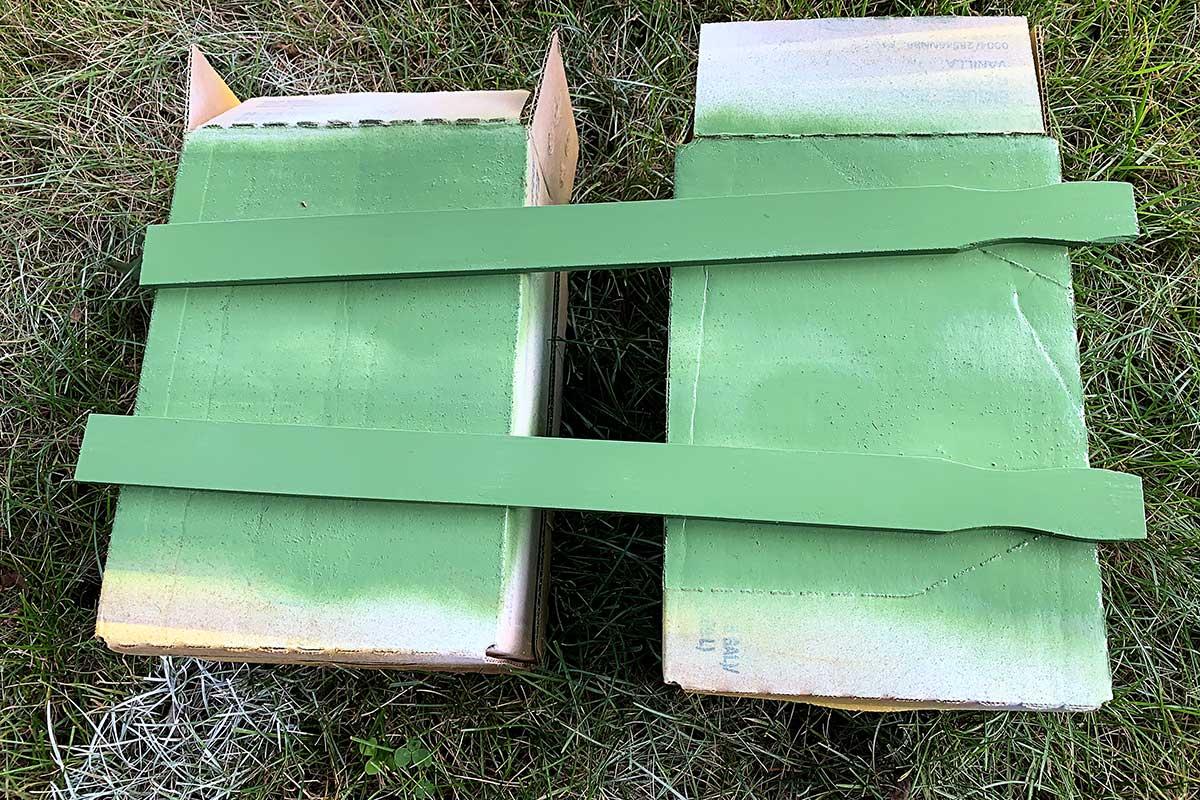 Painting wooden paint stirring sticks green.