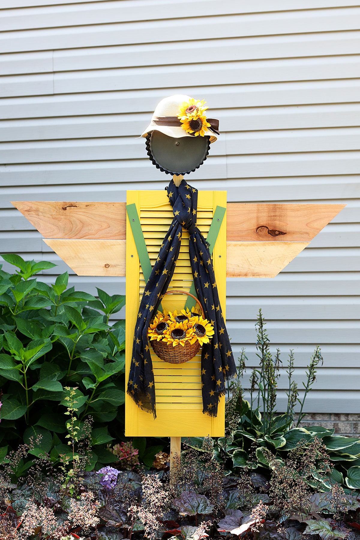 Repurposed scarecrow for the garden using a shutter.