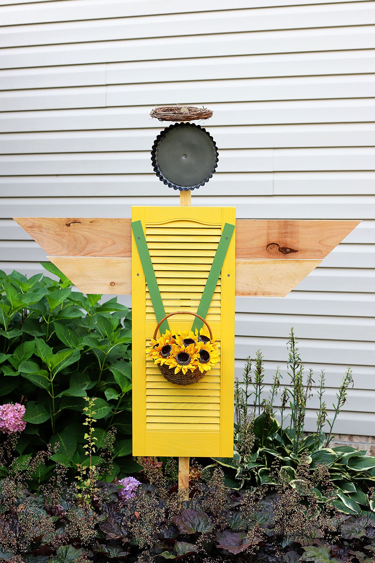 A shutter angel for the garden made with a repurposed shutter from the thrift store. The angel is holding a basket of sunflowers and wearing a halo made from a grapevine wreath.