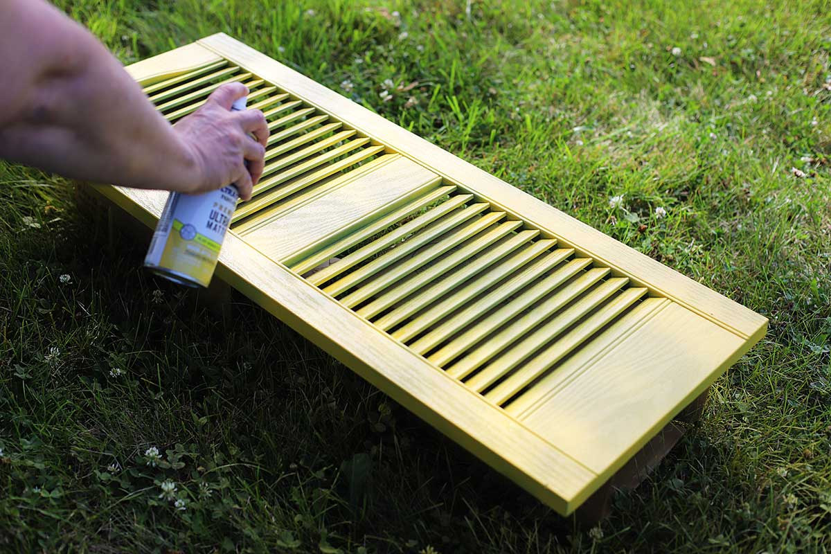Spray painting a shutter yellow.