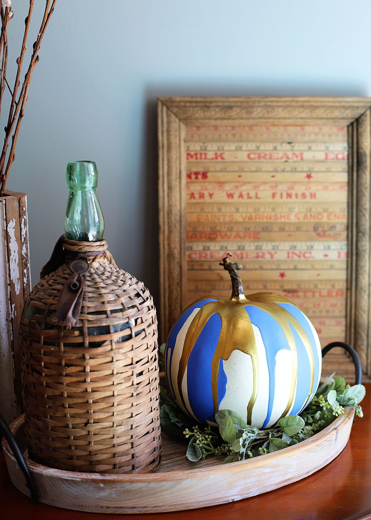 Paint dripped pumpkin setting on a tray with French farmhouse decor.