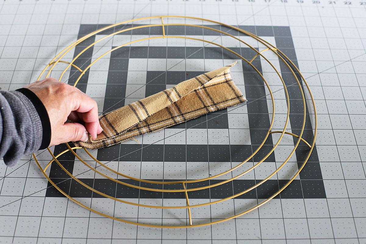 Doblar la tela a lo largo para hacer una corona de trapo.