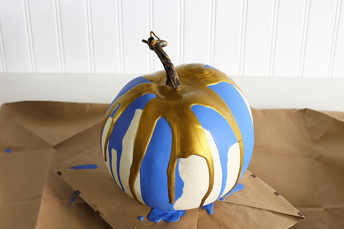Pumpkin with gold and blue paint splatters on it.
