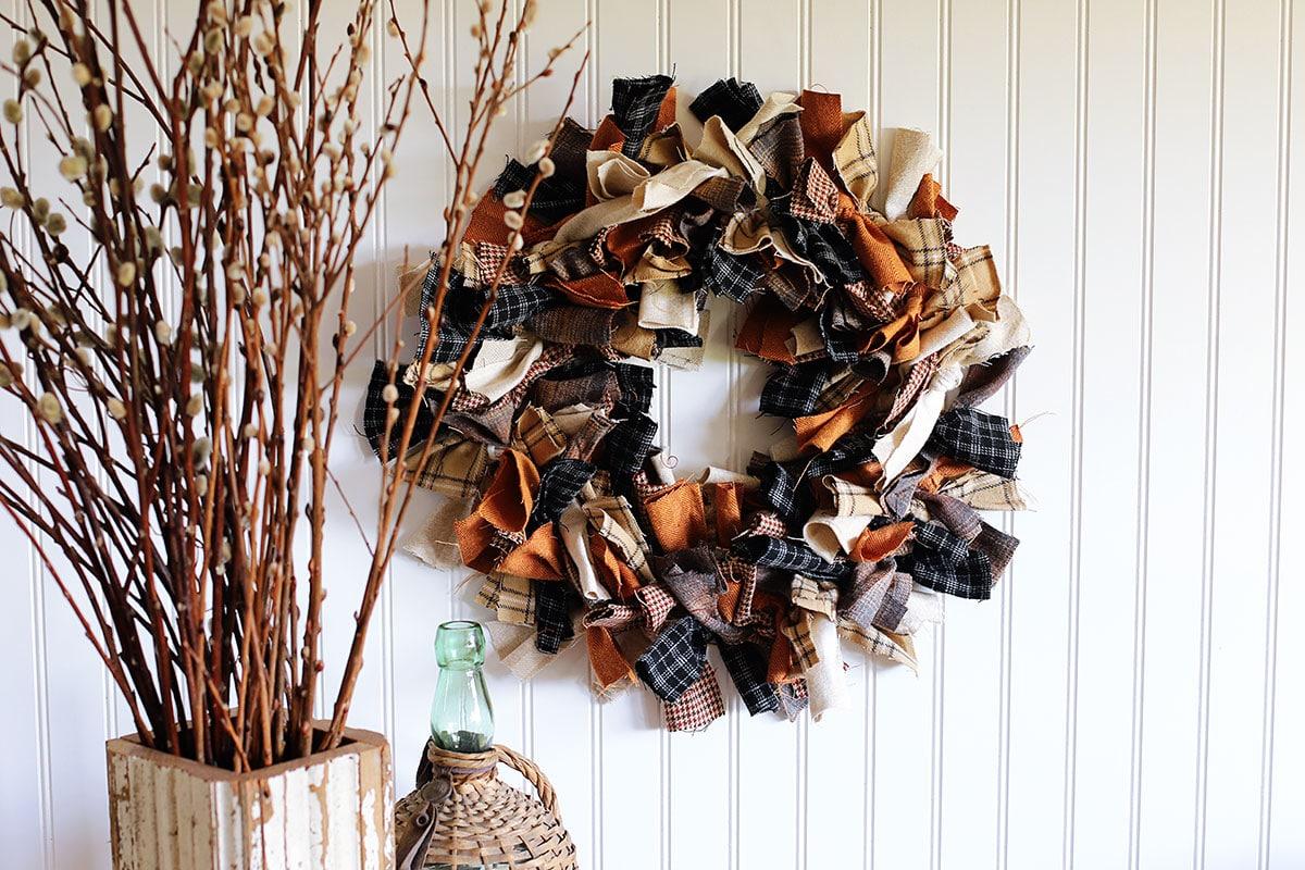 Una corona de trapo hecha con franela estampada en otoño colgada en la pared.