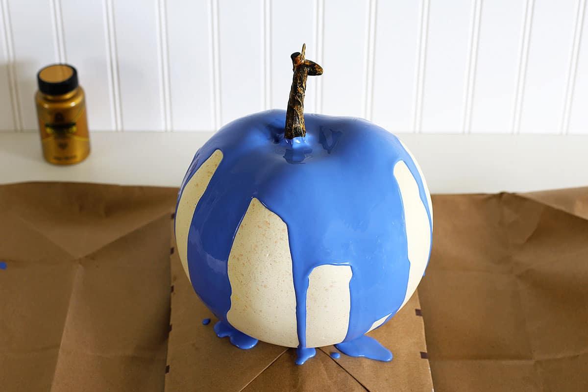 Blue acrylic paint on a paint poured pumpkin.