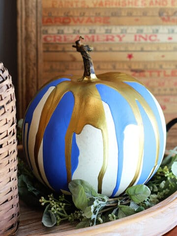 Pumpkin decorated by the paint pouring technique setting on a tray surrounded by rustic farmhouse decor.