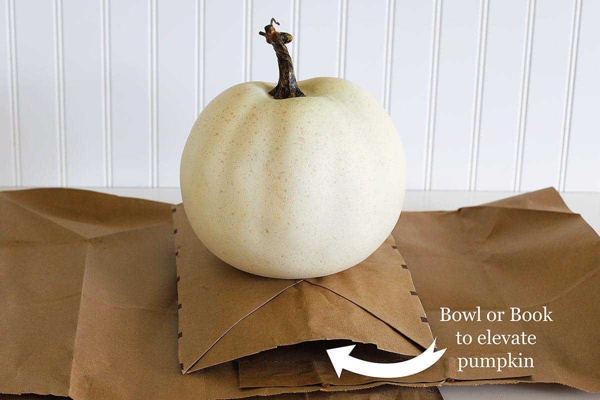 Preparing the surface to pour paint your pumpkins.