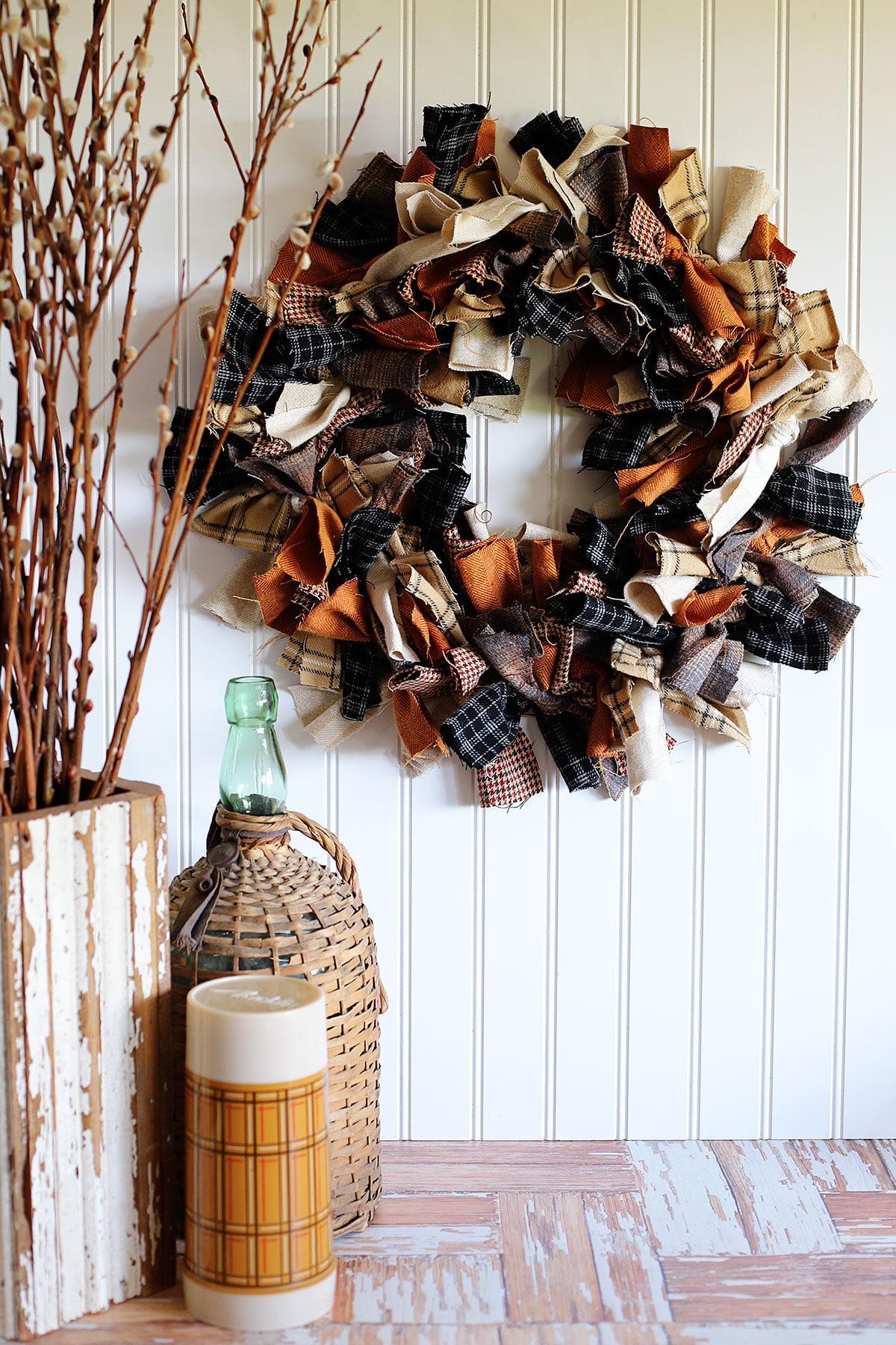 Tutorial para hacer una corona de trapo: muestra una corona de trapo colgada en la pared junto a un jarrón de madera con ramitas, una vieja botella de vino cubierta de mimbre y un termo marrón.