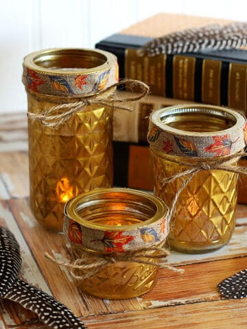 Gold painted quilted jelly jars used as votive holders sitting on a wooden background with feathers and books.