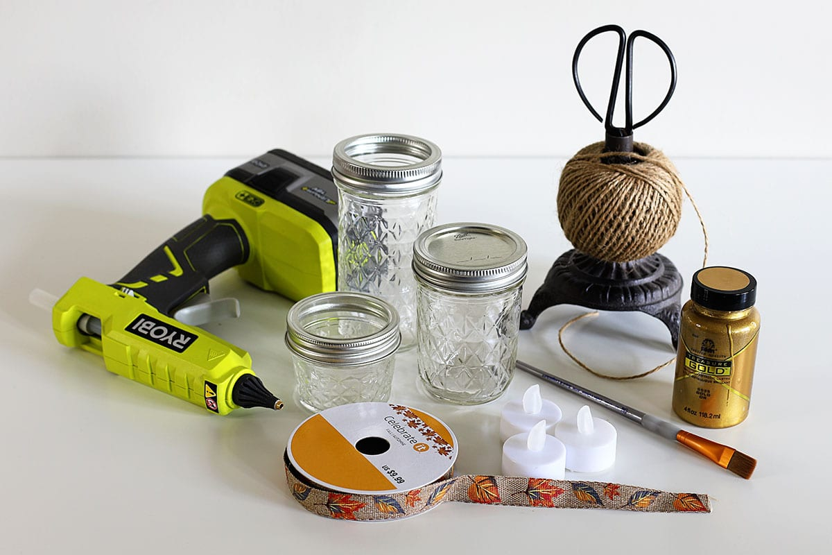 Supplies for making painted mason jar candle holders - Ball jelly jars, metallic gold paint, paintbrush, ribbon, jute twine, scissors, glue gun, battery operated votives.