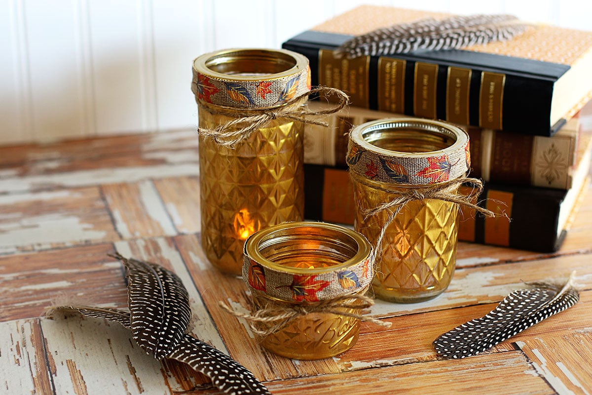 Gold painted mason jars used as votive holders displayed with feathers and books.